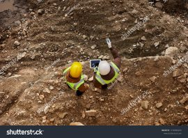 stock-photo-above-view-shot-of-two-industrial-workers-wearing-reflective-jackets-standing-on-mining-worksite-1150690232